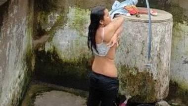Indian village girl bathing near water tank outdoor