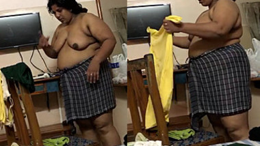 Fat Indian woman with big belly walks around the house with naked boobs
